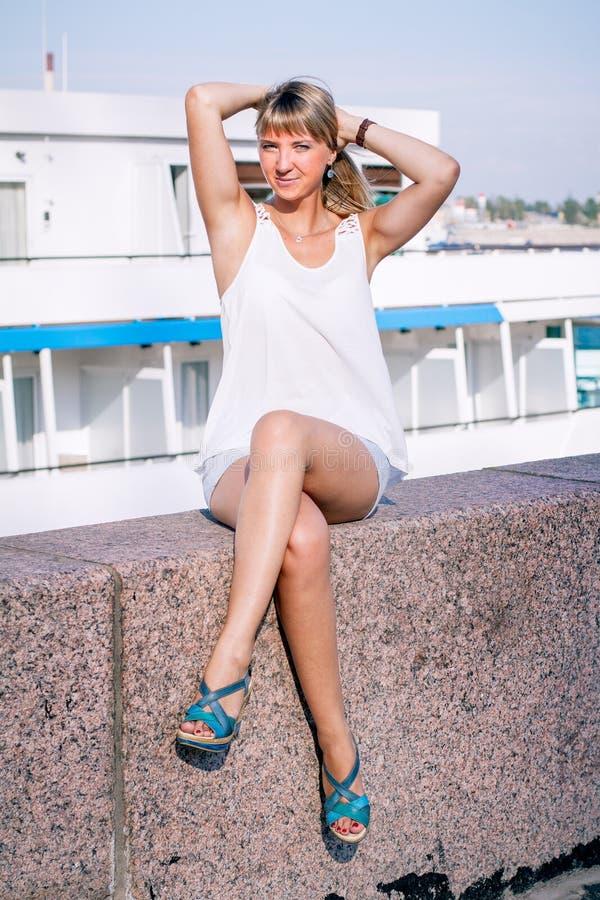 Young beautiful woman sitting on a granite embankment stock photo