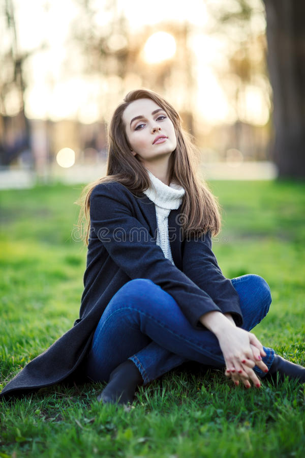 Young beautiful woman sitting on a grass in sun light on sunset royalty free stock images