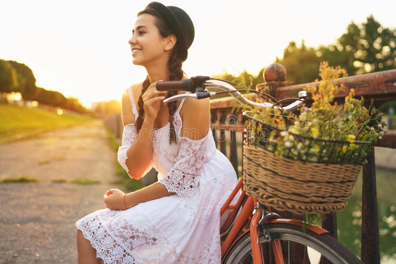 Young beautiful woman sitting on her bicycle with flowers at sun royalty free stock photos