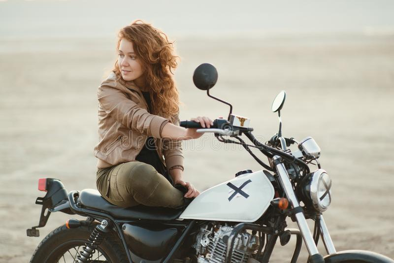 young beautiful woman sitting on her old cafe racer motorcycle in desert at sunset or sunrise stock image