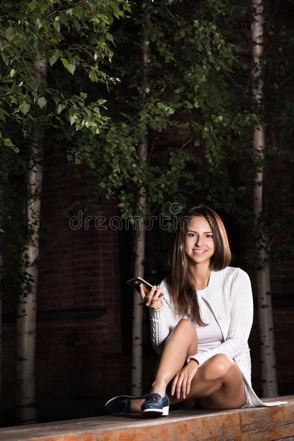 Young beautiful woman sitting on a Park bench with the phone in her hand royalty free stock image