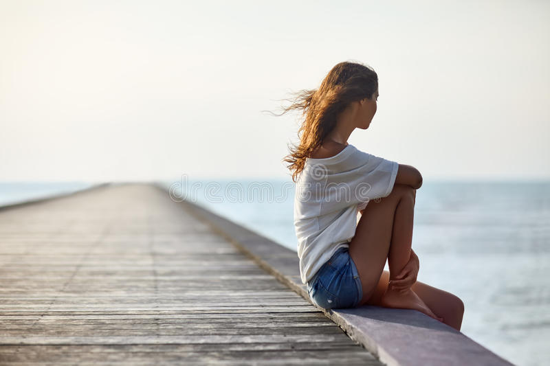 Young beautiful woman sitting on the pier stock photos