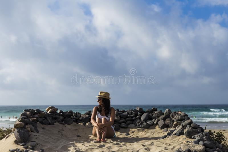 Young beautiful woman sitting on the sand surrounded of volcanic black rocks. Sea background. Horizon Canary islands royalty free stock photos