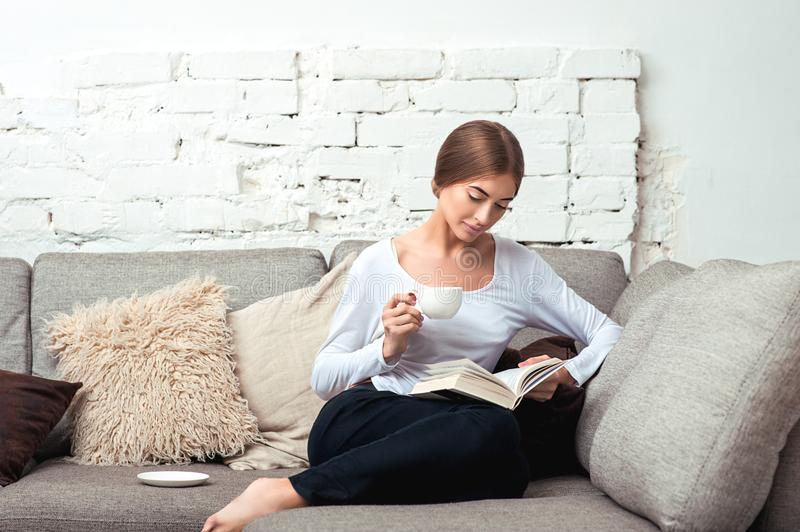 Woman reading a book on sofa stock photo