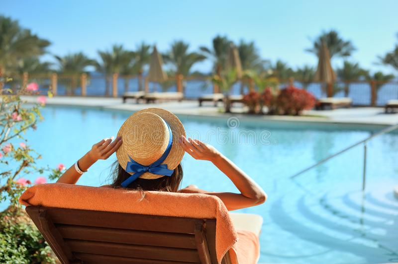 Young beautiful woman Sitting On Sun Loungers By Swimming Pool at the hotel in hat royalty free stock image