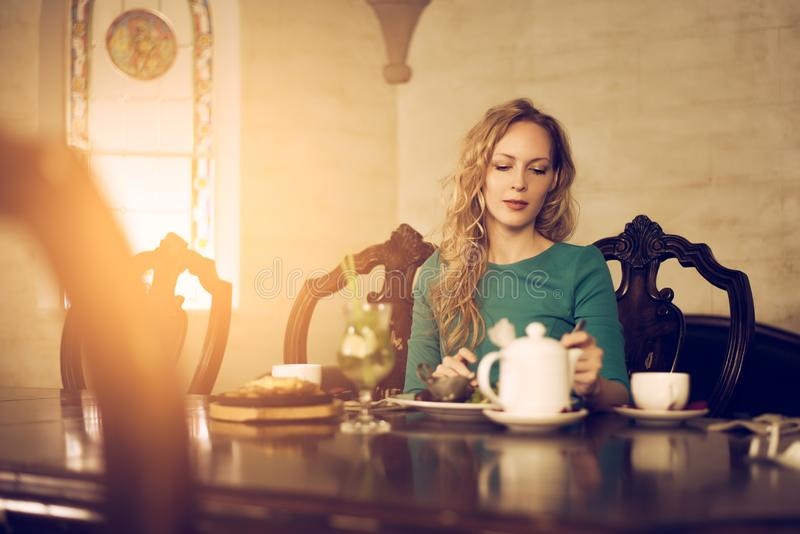 Young beautiful woman is sitting at the table and having dinner in the luxurious luxury interior stock images