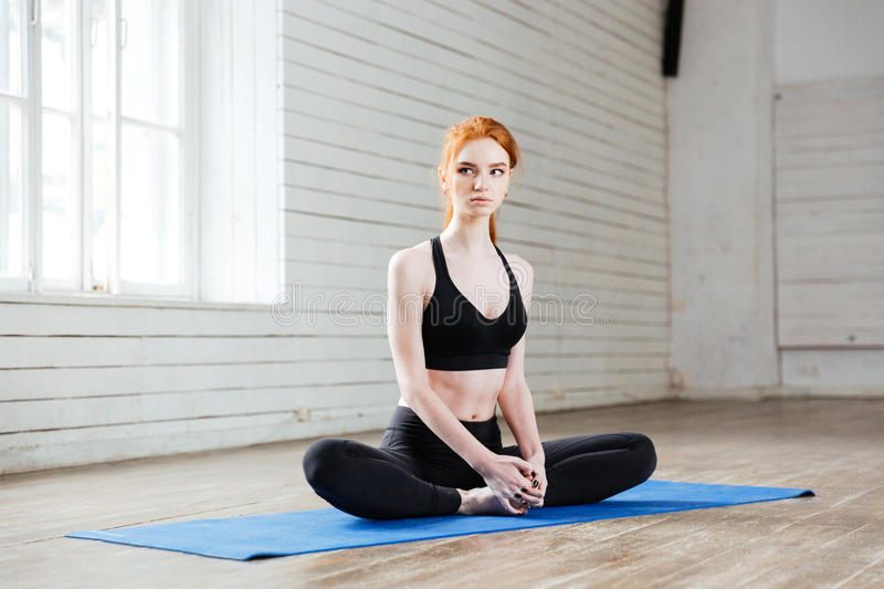 Young beautiful woman sitting in yoga position. In the gym royalty free stock photos