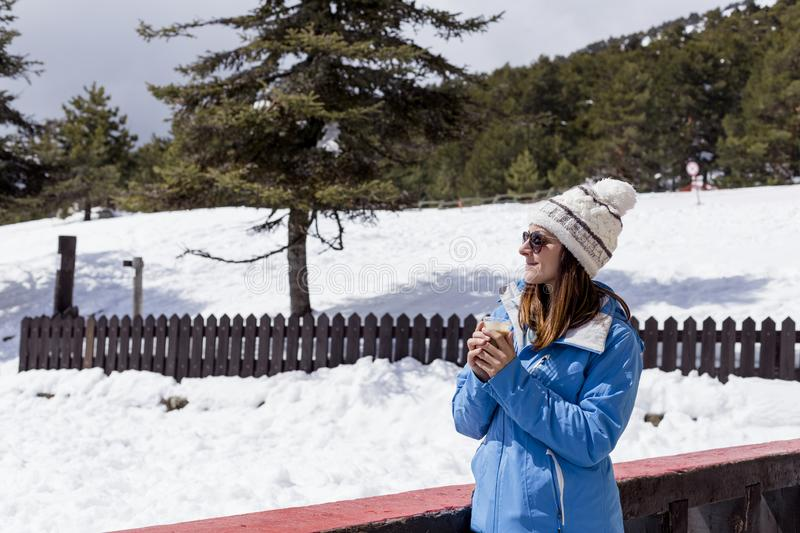 Young beautiful woman with ski equipment relaxing and having a cup of coffee in the mountain. Sunny and cold weather. Nature. Outdoors royalty free stock photo