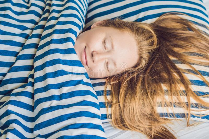 Young beautiful woman sleeping in her bed and relaxing in the mo royalty free stock image