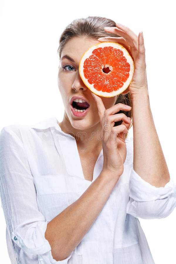 Young beautiful woman with the slice of grapefruit in front of her eye isolated on white background. Curious girl of european appearance in a white shirt looks royalty free stock photos