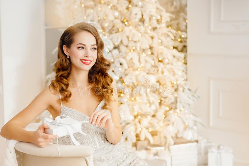 Young beautiful woman is smiling and happy unpacking Christmas present box, white and silver color on yellow bokeh stock images