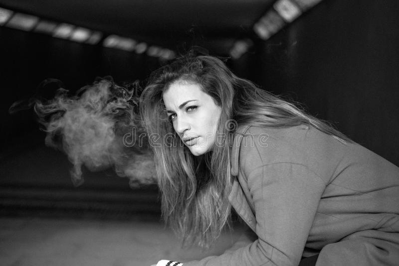 Young beautiful woman smoking cigarette. Close-up Young beautiful woman smoking cigarette royalty free stock images