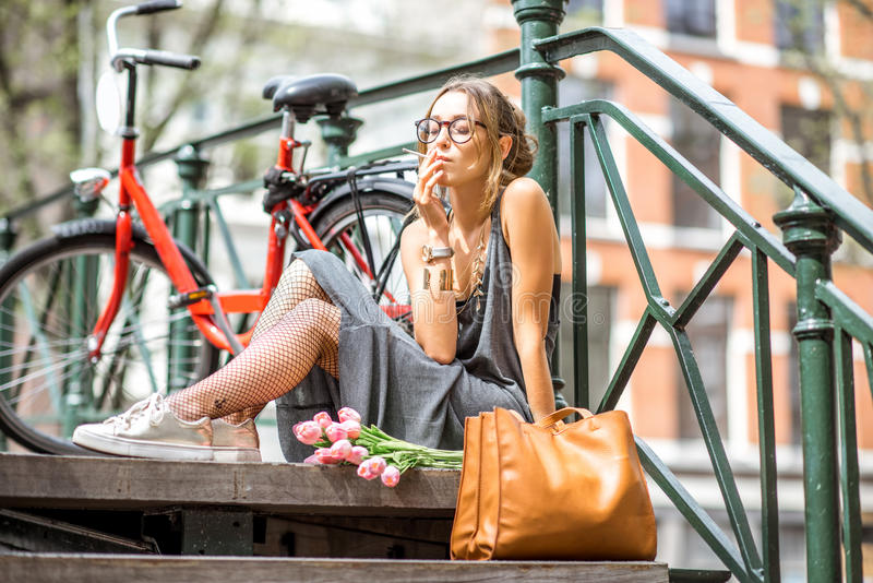 Woman smoking in Amsterdam city. Young beautiful woman smoking a cigarette sitting with flowers and bicycle on the bridge in Amsterdam city stock photography