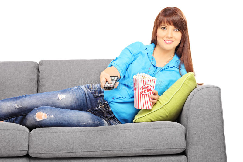 Young Beautiful Woman On A Sofa Watching TV Stock Photo
