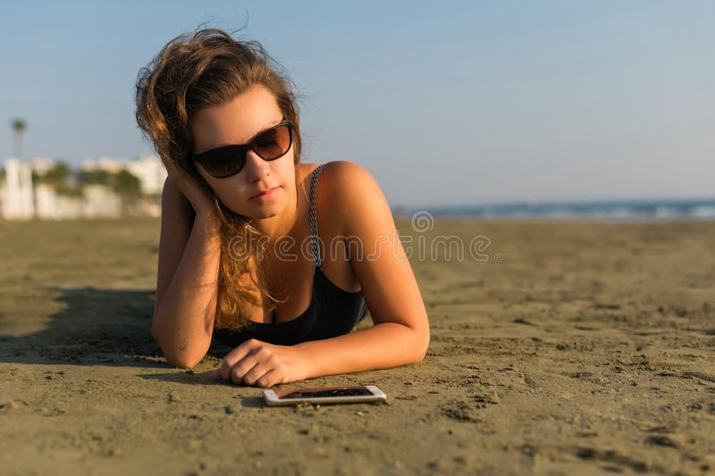 Young beautiful woman in a sports suit and sunglasses lies on the sand. And looks into the mobile phone stock images