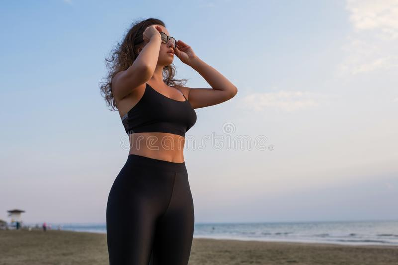 Young beautiful woman in a sports suit and sunglasses standing on the sand on the beach. And looks on the sky stock image