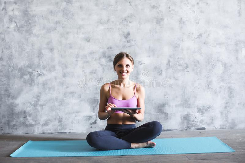 Young beautiful woman in sportswear with a digital tablet in hand on a yoga mat in the gym royalty free stock image