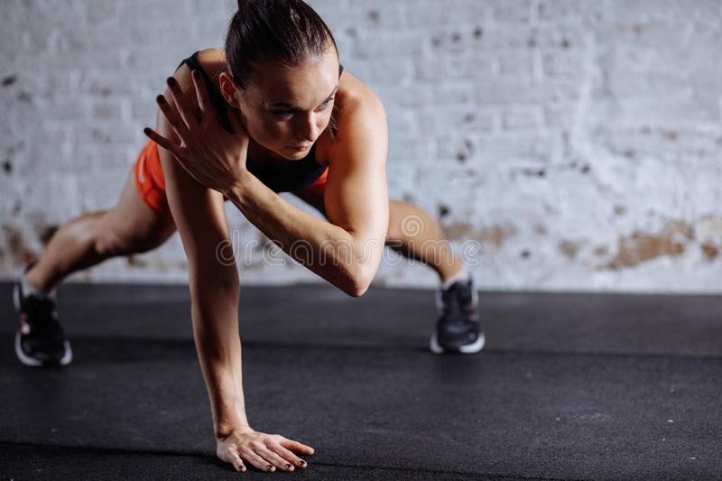 Beautiful woman in sportswear doing plank while trainnig at cross fit gym. Young beautiful woman in sportswear doing one handed plank while trainnig at cross fit royalty free stock photo