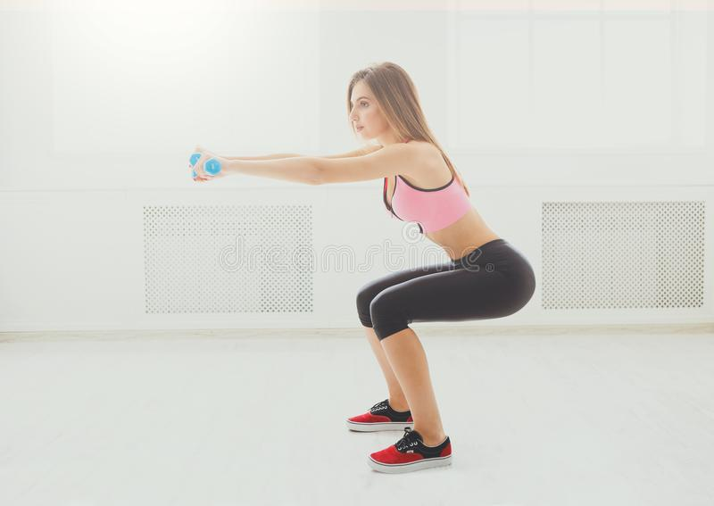 Young beautiful woman in sportswear doing squat royalty free stock image