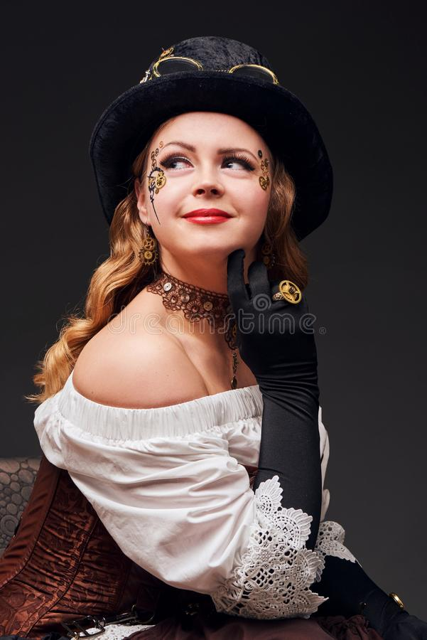 Beautiful woman in steampunk style sitting on the chair stock image