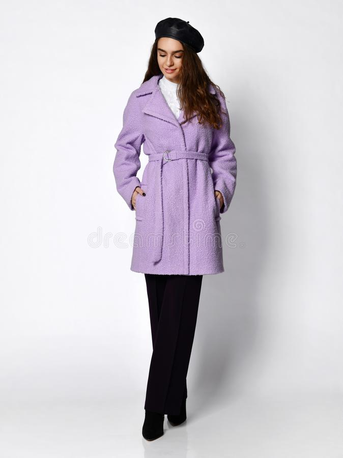 Young beautiful woman step forward in new medium length fashion casual pink winter jacket coat, beret and dark trousers stock photos