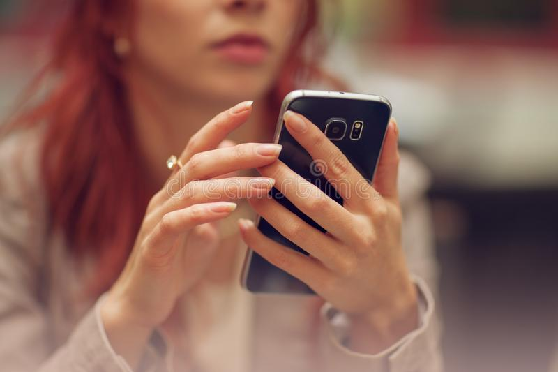 Young beautiful woman in a street cafe, is busy with her cell phone, close up at hands holding mobile phone stock image