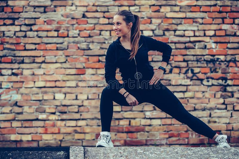 Young beautiful woman stretching her legs, brick wall in the background stock photo
