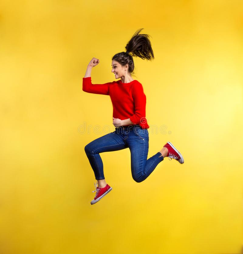 Young beautiful woman in studio, jumping. stock photos
