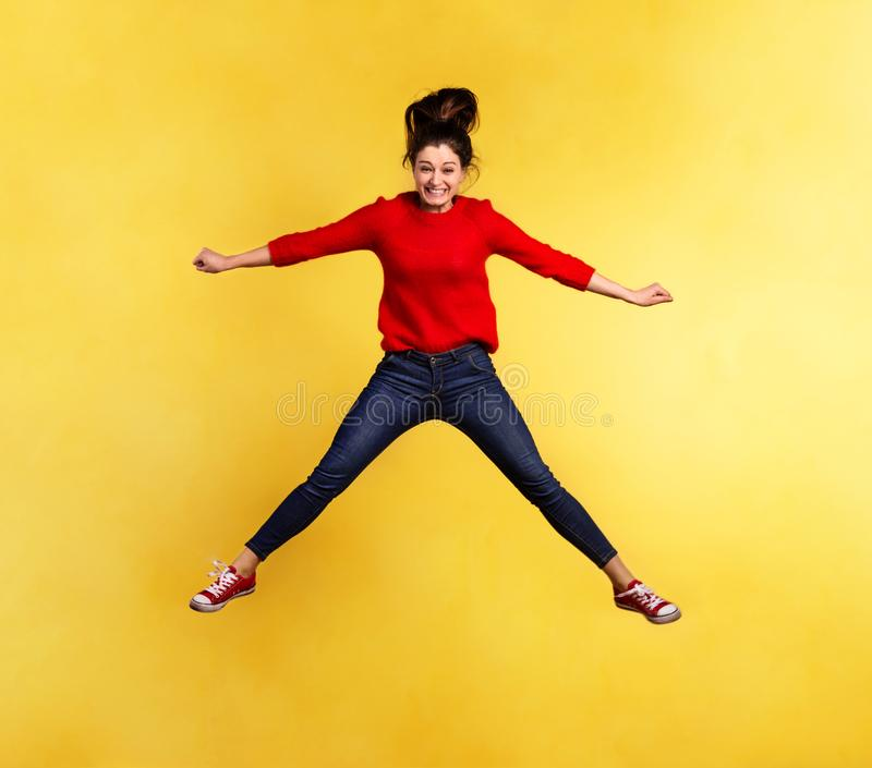 Young beautiful woman in studio, jumping. Young beautiful woman in a studio, jumping. Yellow background. Copy space stock photos