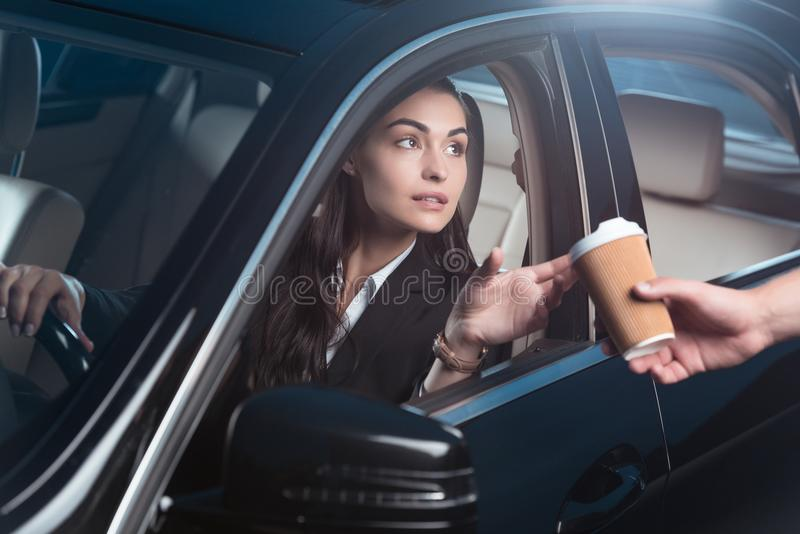 Young beautiful woman in suit sitting in driver seat of car and receiving coffee from stock images