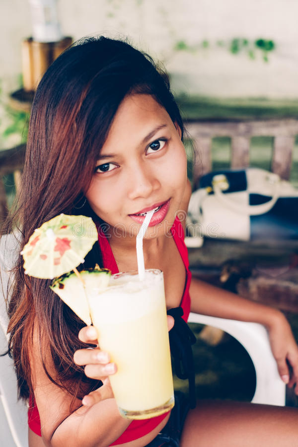 Young beautiful woman on summer vacation on the beach drinking cocktail with pineapple stock photography