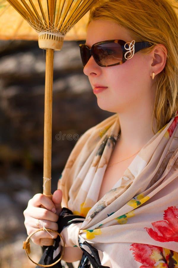 Young beautiful woman sunbathing near sea with sun umbrella stock photo