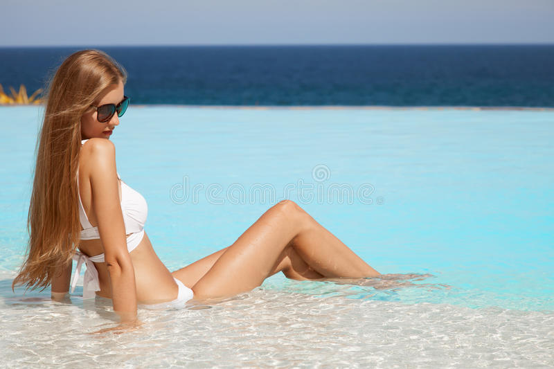Young beautiful woman sunbathing in swimming pool. Nice sea view. Young beautiful woman in white bikini sunbathing in swimming pool. Nice sea view royalty free stock images