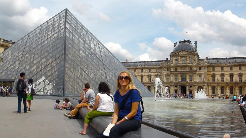 Young beautiful woman in surroundings of Louvre museum royalty free stock images
