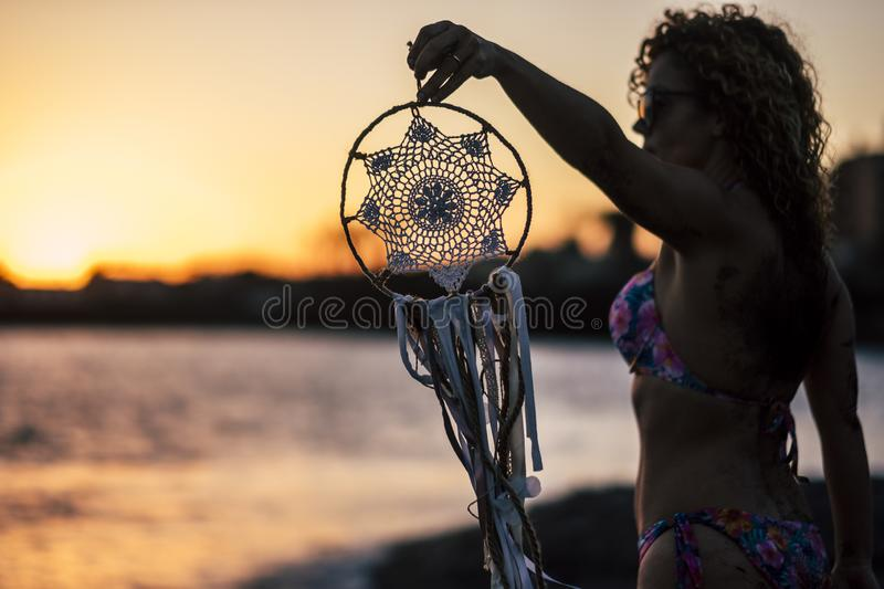 Young beautiful woman take a dreamcatcher during the wonderful sunset at the beach in front of the ocean. feeling with the nature stock photography