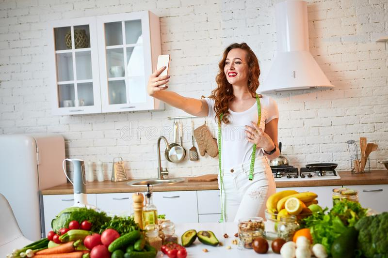 Young beautiful woman take a selfie while cooking in the modern kitchen. Healthy food and Dieting concept. Losing Weight stock image