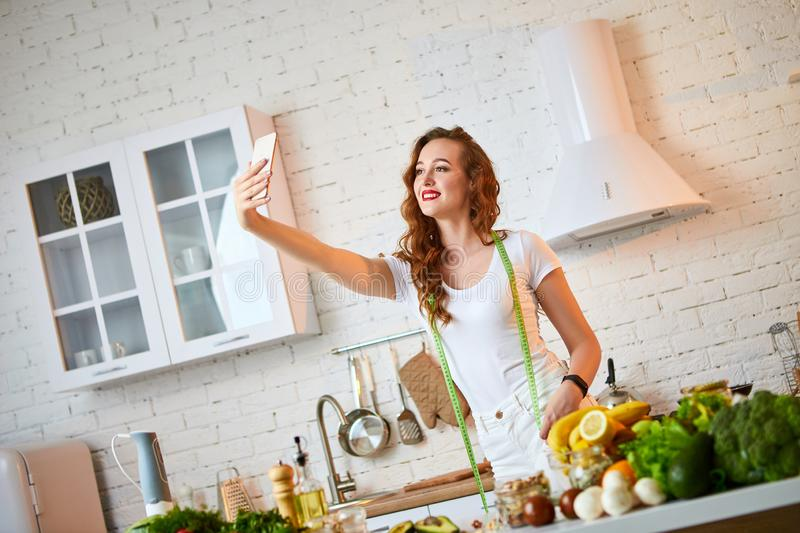 Young beautiful woman take a selfie while cooking in the modern kitchen. Healthy food and Dieting concept. Losing Weight stock photos