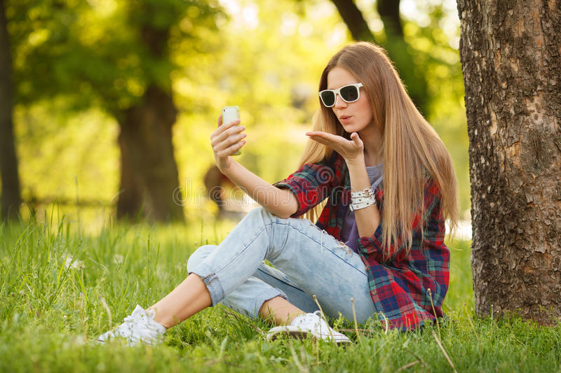 Young beautiful woman takes selfie on cell phone sitting on grass in summer city park. Blow kiss. Beautiful modern girl in stock photo