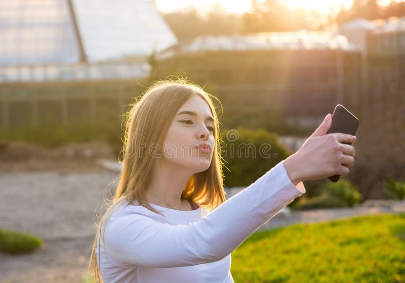 A young beautiful woman taking duck face selfie at sunset. A young beautiful woman taking duck face selfie in a park at sunset royalty free stock images