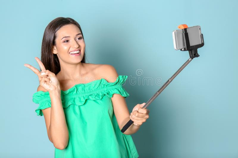 Young beautiful woman taking selfie. Against color background stock images