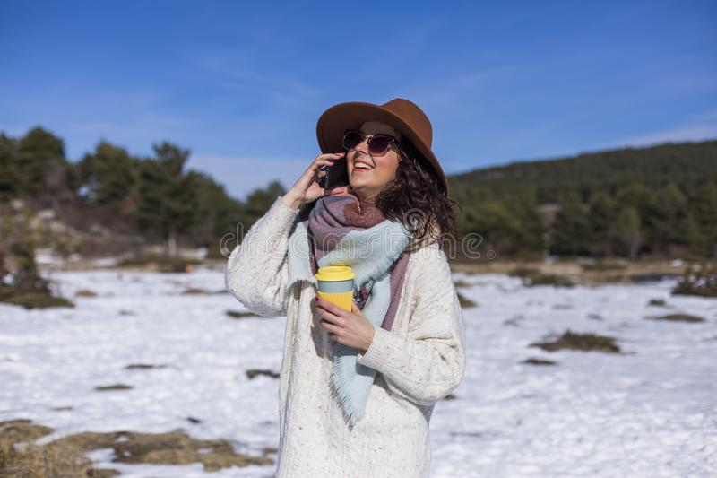 Young beautiful woman talking on her mobile phone in the snow and holding a cup of tea or coffee. Outdoors portrait, lifestyle stock images