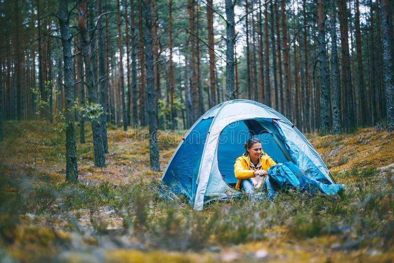 Young beautiful woman with a tent in the forest, camping, solo travel, nature concept stock images