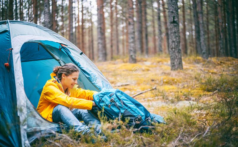 Young beautiful woman with a tent in the forest, camping, solo travel, nature concept royalty free stock image