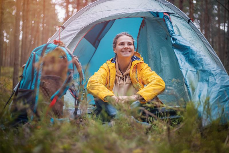 Young beautiful woman with a tent in the forest, camping, solo travel, nature concept royalty free stock images
