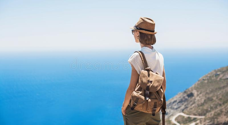 Young woman traveler looking at the sea. Beautiful girl enjoying nature. Summer holidays, vacations, travel, tourism concept stock photo