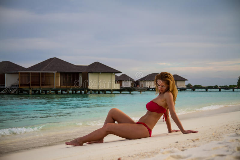 Young beautiful woman on a tropical sunset beach. Maldives beach with a young woman panorama. Luxury water villas, in exotic blue lagoon. Full screen screen stock photos
