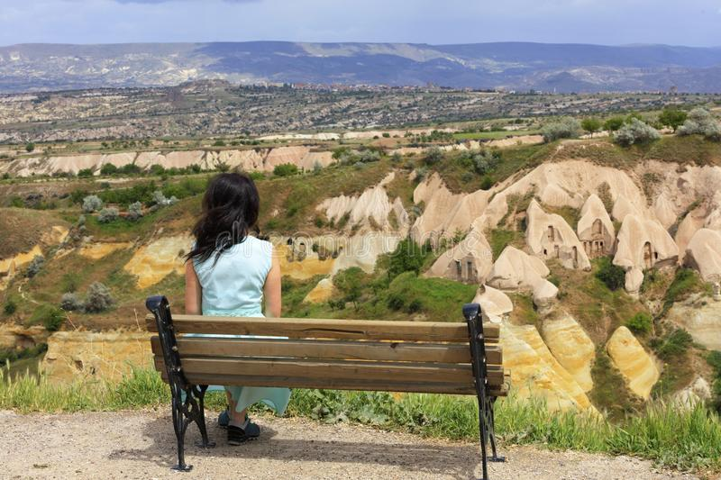 A young beautiful woman in a turquoise dress sits on a wooden bench on a hill against the blurred landscape of mountain caves in royalty free stock images