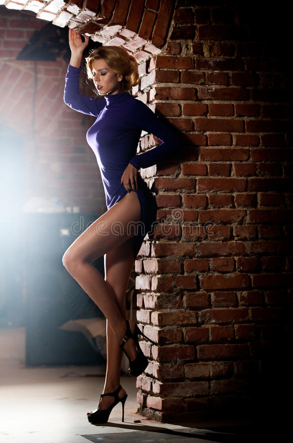 Young beautiful woman in turtleneck short tight fit dress against old red brick wall. Elegant romantic mysterious lady. With long legs on high heels, side view royalty free stock photos