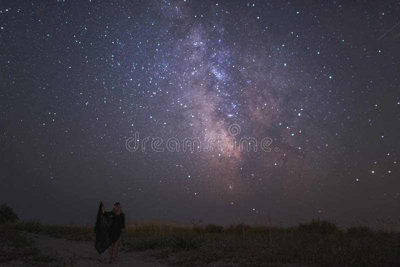 Young beautiful woman under stars of Milky Way Galaxy royalty free stock photography