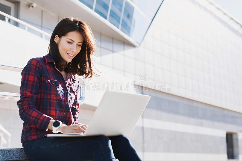 Young beautiful woman using laptop computer in the city street. Pretty happy girl working on laptop outdoor. royalty free stock images